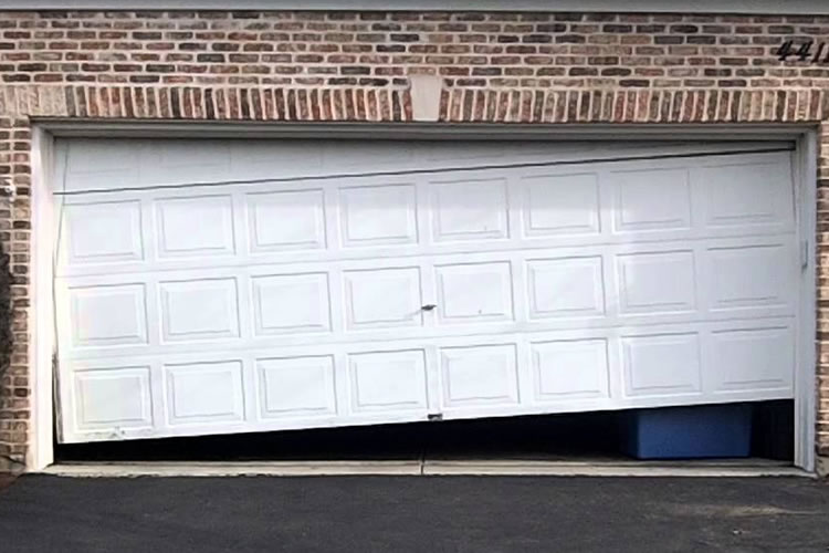 Damaged garage door due to broken spring or cable